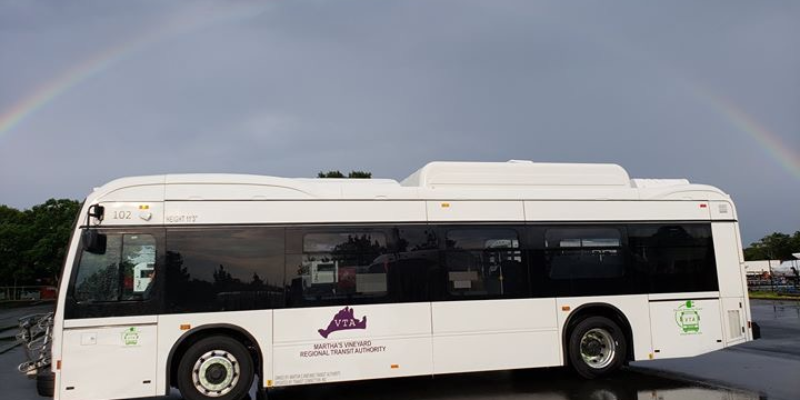 Electric bus with a rainbow in the sky